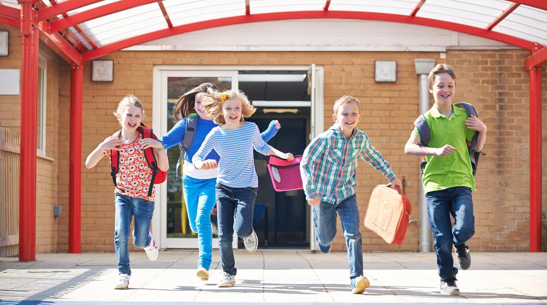 Hitzefrei: Junge Schüler rennen freudig aus der Schule
