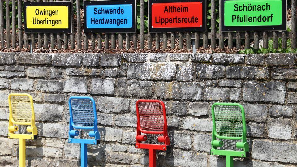 bunte Stühle mit Ortsschildern