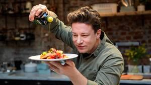 Jamie Oliver gießt Olivenöl über einen Teller mit Essen