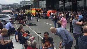 Reisende harren vor dem Gebäude des Hamburger Flughafens aus - teilweise mit gepackten Koffern