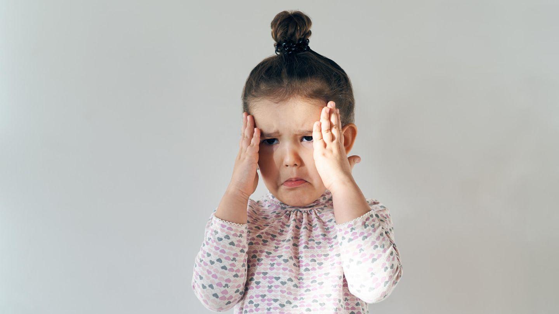 Ein kleines Mädchen mit Dutt weint
