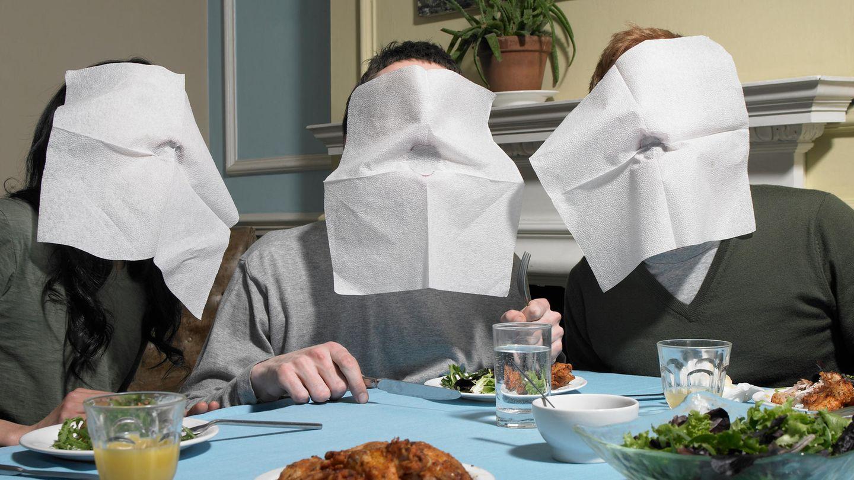 Drei junge Menschen essen an einem Tisch und haben Servietten vor ihren Mündern