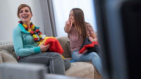 Zwei junge Frauen schauen zusammen Fußball im Fernsehen