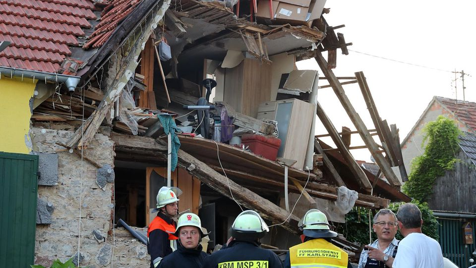 Feuerwehrleute stehen in Himmelstadt vor einem nach einer Verpuffung eingestürzten Wohnhaus