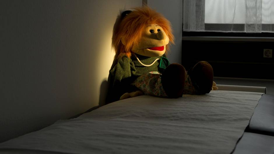 Ein Stofftier liegt im Dunkeln auf einem Bett