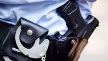 Ein Polizist mit Handschellen und Pistole am Gürtel in Köln