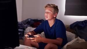 Ein Junge sitzt vor einem Bildschirm und spielt Computerspiele