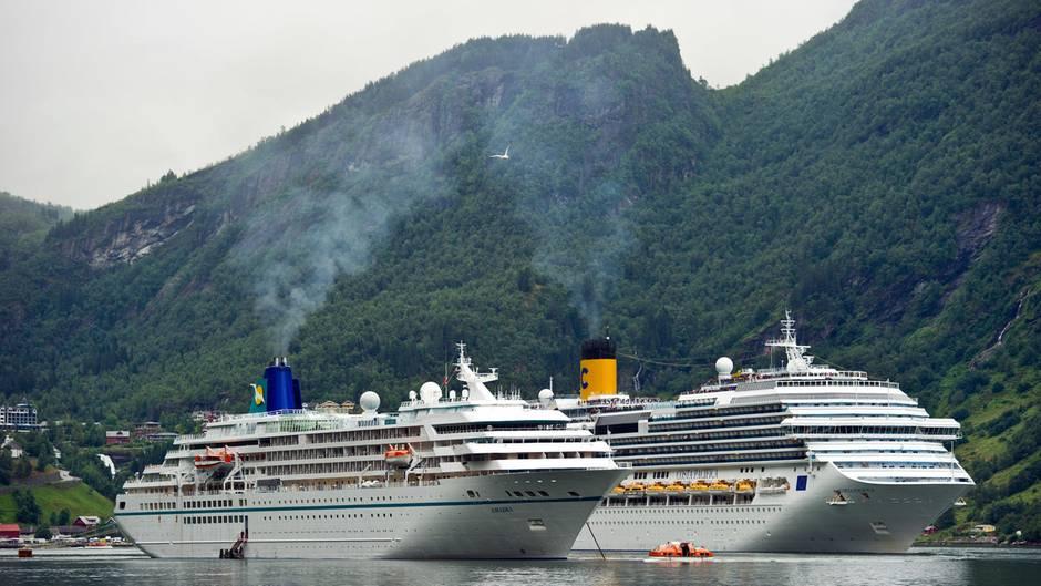 """Zwei Kreuzfahrtschiff mit Abgasfahnen liegen im Geirangerfjord auf Reede: Die """"Amedea"""" von Phoenix Reisen und die """"Costa Pacifica"""" der Reederei Costa Crociere."""