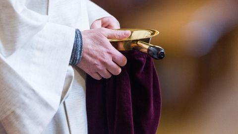 Ein Messdiener sammelt Geld beim Gottesdienst