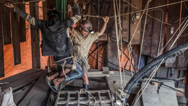 Zwei Männer hängen über einem Mineneinstieg