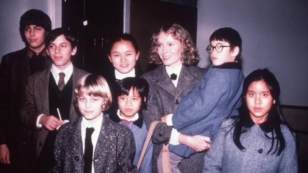 Mia Farrow hatte insgesamt 14 Kinder, zehn davon adoptiert. Drei der Adoptivkinder sind mittlerweile gestorben. Auf diesem Bild von Silvester 1984 sind zu sehen (v. l.): Sascha, Matthew und Fletcher (alle drei leibliche Kinder aus Mias Ehe mit André Previn), Soon-Yi (adoptiert 1978; seit 1997 verheiratet mit Woody Allen), Daisy (adoptiert 1976), Moses (adoptiert 1980; seit 1991 auch Allens Adoptivsohn) und Lark (adoptiert 1973; gestorben 2008). Weitere Kinder: Dylan (adoptiert 1985), Ronan (geboren 1987), Tam (adoptiert 1992, gestorben 2000), Isaiah (adoptiert 1992), Thaddeus (adoptiert 1994, gestorben 2016) sowie Quincy (adoptiert 1994) und Frankie-Minh (adoptiert 1995)