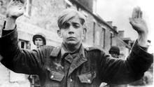 Für ihn ist der Krieg vorbei  Mit erhobenen Händen ergibt sich ein junger deutscher Schütze in der Normandie amerikanischen Truppen