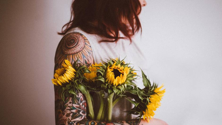 Eine tättowierte Frau hält Blumen im Arm