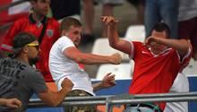 Ein Mann in weißem T-Shirt schlägt mit geballten Fäusten auf einen Mann im roten T-Shirt ein