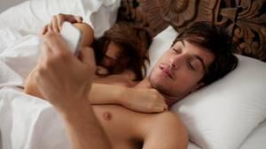 Mann und Frau im Bett mit Handy