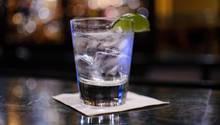 Cocktailglas mit Eiswürfeln und Limette