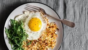 Spiegelei, Kartoffeln und Salat liegen auf einem Teller