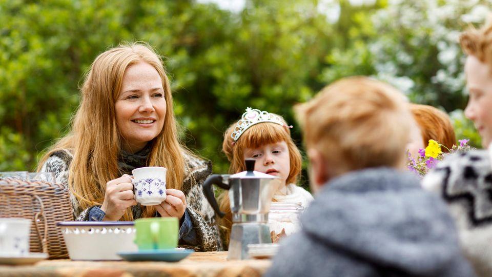 Eine Mutter sitzt mit vier Kindern am Tisch