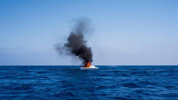 Nachdem die Flüchtlinge in Sicherheit gebracht wurden, brennendie Helfer die Boote ab – damit sie nicht wieder in die Hände von Schleusern fallen