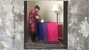 Eine ältere Dame steht am Bügelbrett und bügelt eine Flagge