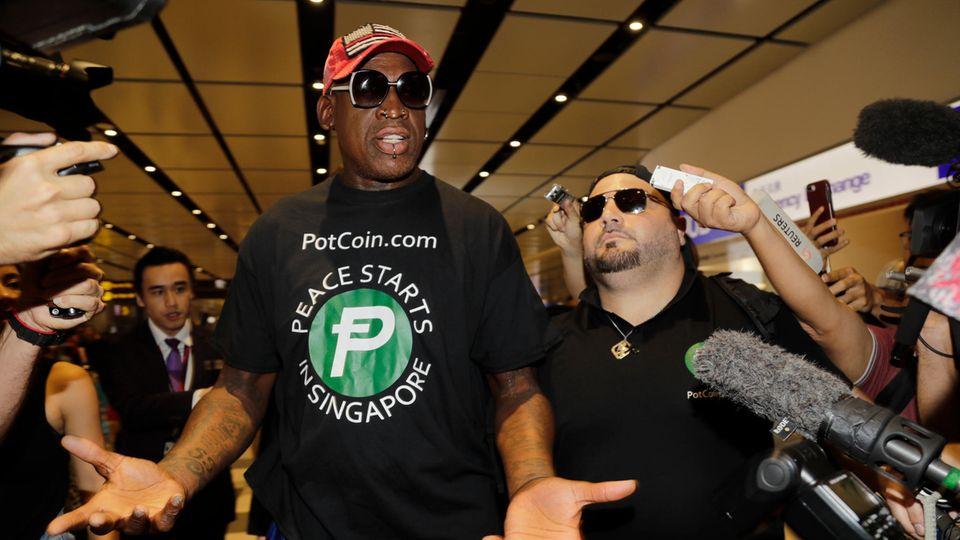 Ex-Basketball-Star Dennis Rodman (M.) spricht nach seiner Ankunft auf dem Flughafen mit Journalisten