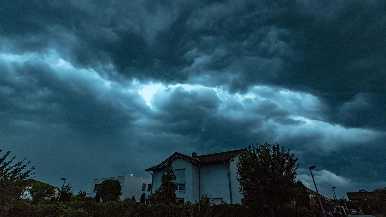 Unwetter heute: Dunkle Gewitterwolken ziehen am Montagabend über ein Wohngebiet in Straubing, Bayern.
