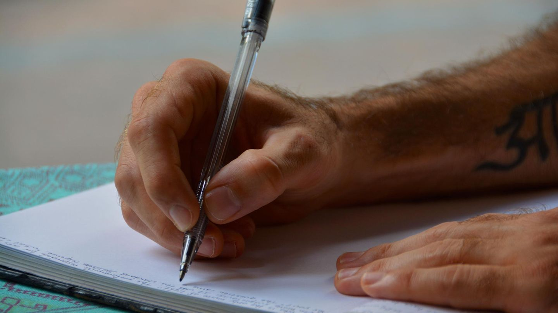 Mann schreibt mit Kugelschreiber in ein Buch