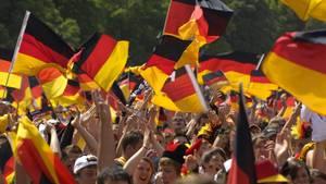 Menschen mit Deutschland-Fahnen jubeln beim Public Viewing