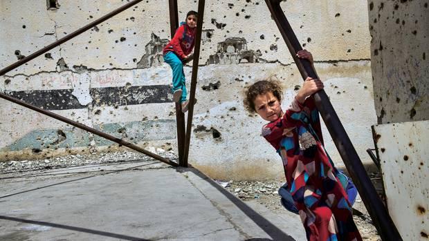 Kinder spielen im Hof der Houari-Boumedienne-Schule, die während der Kämpfe stark beschädigt wurde. Im Haus gegenüber residierte die Religionspolizei des IS