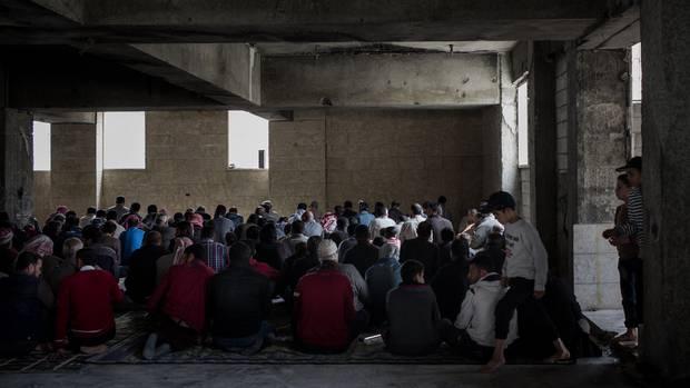 Männer beten in einer zerstörten Moschee