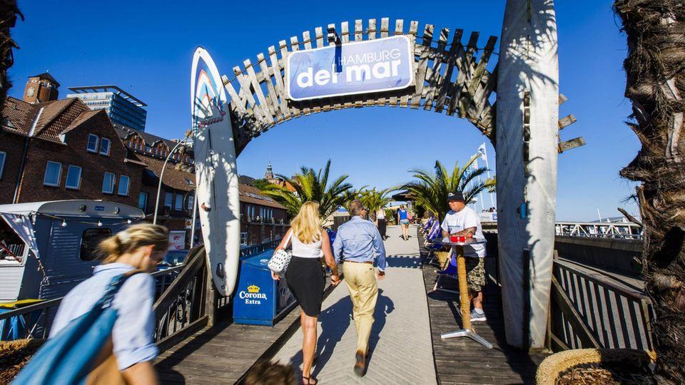 Bild 1 von 10der Fotostrecke zum Klicken:Hamburg: Hamburg del Mar  Gleich an den St. Pauli Landungsbrücken erhebt sich über der Elbe dieser 1000 Quadratmeter große Beach Club, von dem man mit einem Cocktail in der Hand unterm Sonnenschirm das Treiben im Hafen überblicken kann.  Infos:www.hamburg-del-mar.de