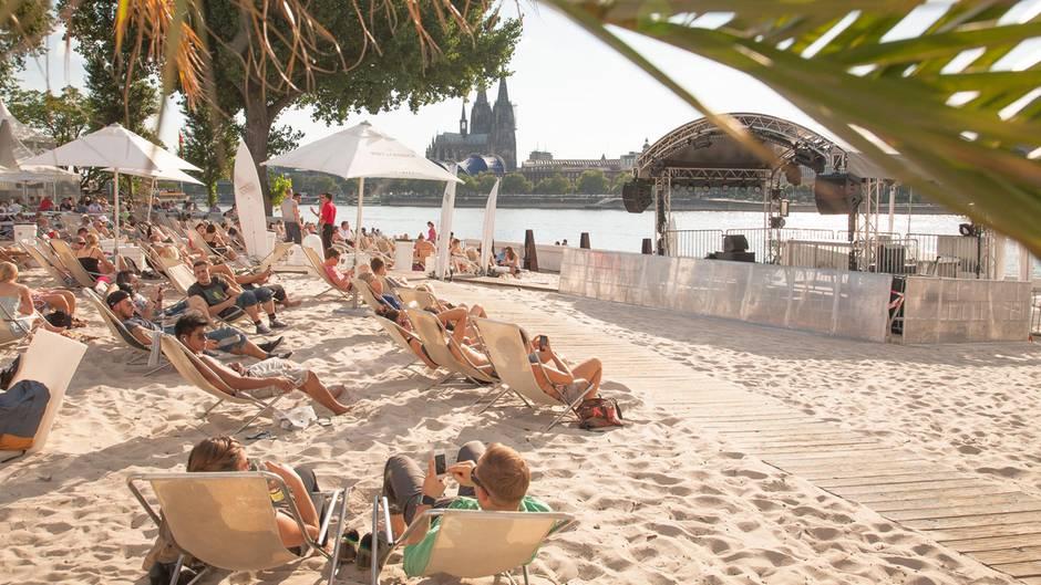 Köln: KM 689   Der Cologne Beach Club liegt am rechten Rheinufer, bei Flusskilometer 689 im Stadtteil Deutz: Von hier aus blicken die Gäste auf die Skyline mit dem abends angestrahlten Kölner Dom. Neben den Drinks gibt es Currywurst und mexikanische Nachos für den kleinen Hunger.  Infos: www.km689.de