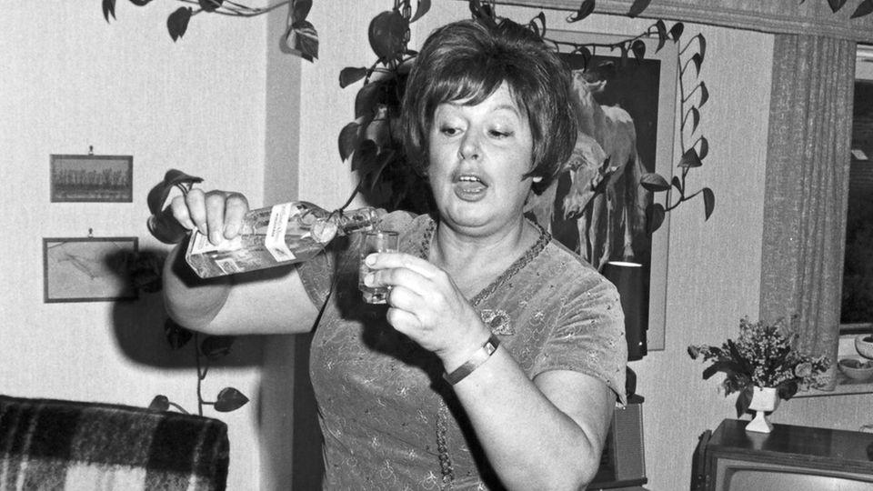 Eine Frau trinkt einen klaren Schnaps