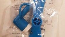 Ein kleiner blauer Ventilator mit USB-Anschluss liegt in einem Plastikbeute auf einer weißen Fläche