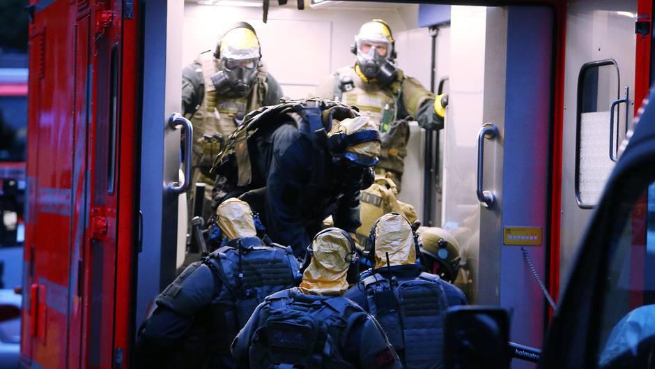 Polizisten in Schutzanzügen vor dem Kölner Hochaus, in dem sie Rizin fanden