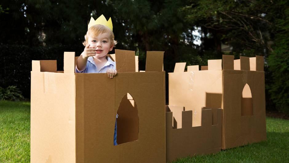 Ein kleiner Junge mit Krone auf dem Kopf in einem Schloss aus Pappe