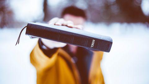 Ein junger Mann hält sich eine Bibel vor das Gesicht