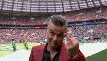 Robbie Williams steht im roten Jackett mit Leo-Print auf der Bühne und hält seinen Mittelfinger in die Kamera