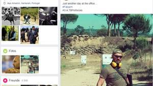 Ein muskulöser Mann mit Sonnenbrille und Ohrschützern posiert mit einem schweren Gewehr auf einem Schießplatz