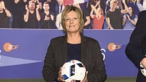 ZDF-Kommentatorin steht im dunklen Blazer und mit Fußball in den Händen in einem TV-Studio