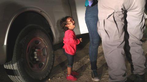 Ein kleines Mädchen aus Honduras sieht weinend zu, seine Mutter von einer texanischen Grenzbeamtin durchsucht wird