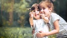 Zwei Mädchen spielen auf einer Wiese
