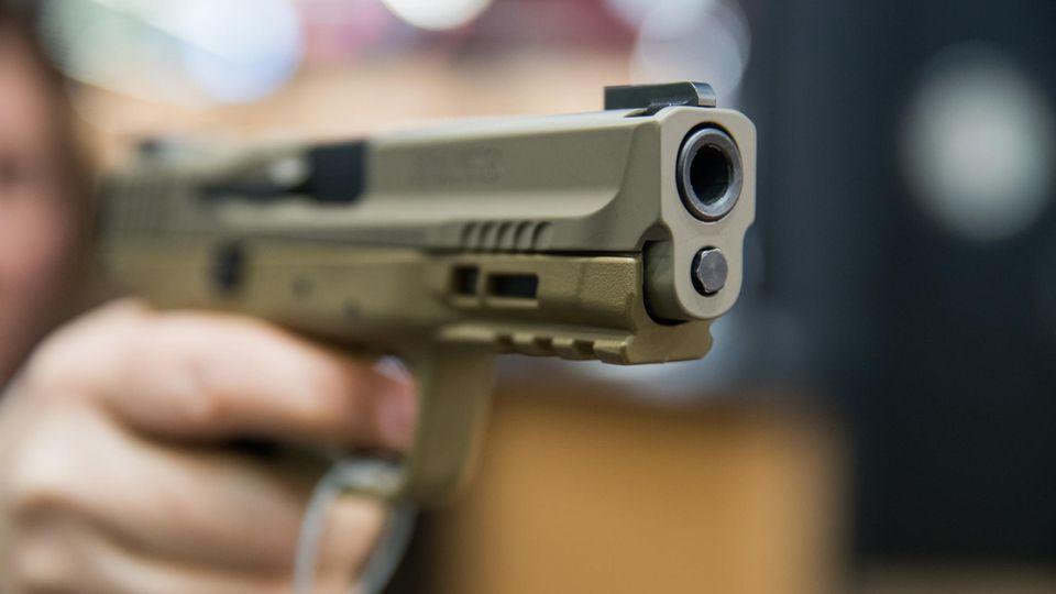 Frau hält Handfeuerwaffe