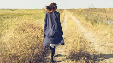 Eine Frau geht über einen Feldweg