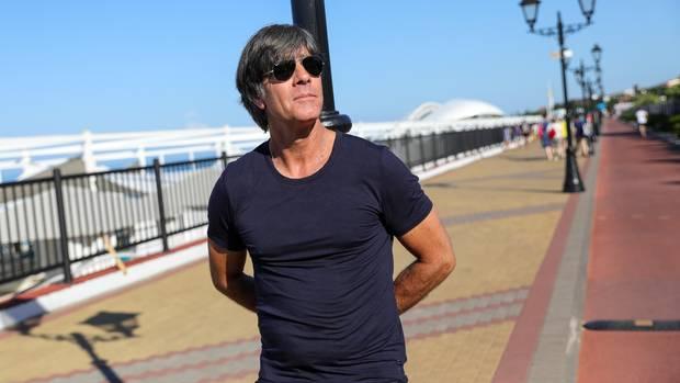 Tiefenentspannt lehnt Bundestrainer Joachim Löw an einer Laterne in Sotschi, den Blick in die Weite schweifen lassend