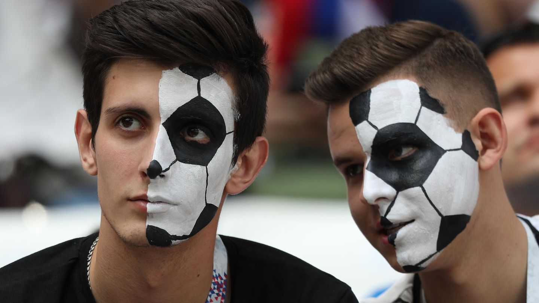 Fußballfans, die sich ein Ballmuster ins Gesicht geschminkt haben