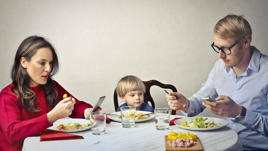 Vater, Mutter, Kind beim Essen, beide Erwachsene halten Smartphones in den Händen