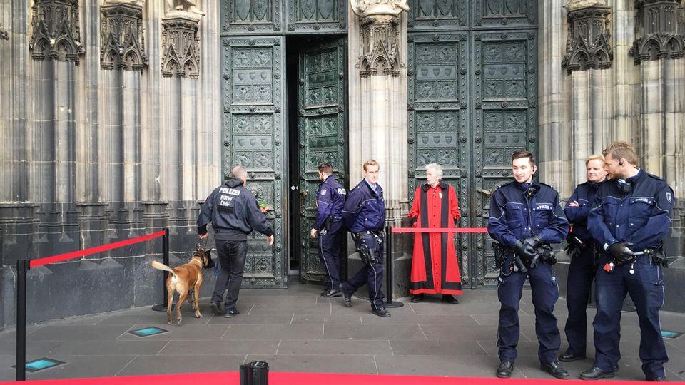 Ein Polizist geht mit einem Spürhund in den gesperrten Dom