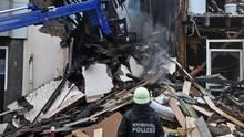 Ein Beamter der Kriminalpolizei betrachtet die Trümmer eines Hauses, in dem es in der Nacht eine Explosion gegeben hat. Bei einer Explosion in einem Wohnhaus in Wuppertal sind 24 Menschen verletzt worden.