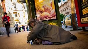 Ein obdachloser Bettler vor einem Werbeschild